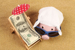 Summer piggy bank with sunglasses and hankie next to beach chair with towel from greenback hundred dollars and red parasol on sand. Beach Royalty Free Stock Photo