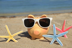 Summer piggy bank with sunglasses Stock Image