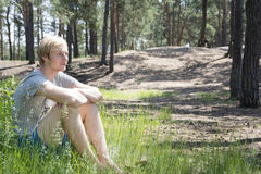 In summer, the pine forest sitting on the grass blond man. Stock Photos