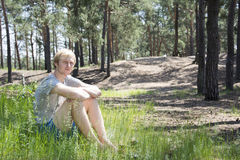 In summer, the pine forest sitting on the grass blond man. Royalty Free Stock Photos