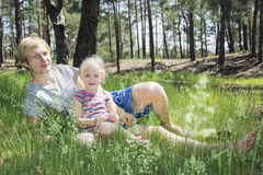 In summer, the pine forest sitting on the grass blond man with a Stock Images