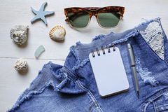 Summer planning concept- jeans shorts, sunglasses, seashells and notebook Stock Images