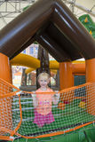 Summer at the playground on a trampoline plays a little girl. Royalty Free Stock Photo