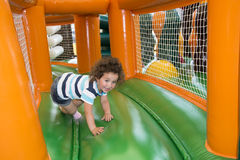 Summer at the playground on a trampoline plays a little girl. stock image