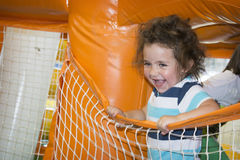 Summer at the playground on a trampoline plays a little girl. Stock Photo