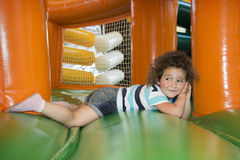 Summer at the playground on a trampoline plays a little girl. Royalty Free Stock Photography