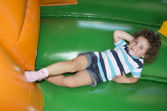Summer at the playground on a trampoline plays a little girl. Royalty Free Stock Images