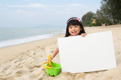 Summer playtime. Little child girl holds a white board at beach Stock Photography