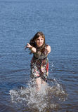 Summer pleasure. The girl plays with water in summer lake Stock Photo
