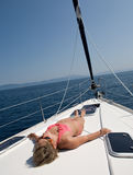 Summer pleasure. Woman in pink swimsuit lying sunbathing on deck of yacht Stock Images