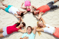 Summer pleasure. Six friends having rest on sandy beach Royalty Free Stock Images
