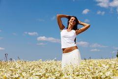 Summer pleasure. Pretty woman posing in front of the camera on a summer meadow Royalty Free Stock Photos