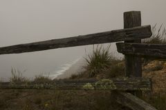 Summer at Point Reyes. A peak through the fog at the waves and seashore of Point Reyes National Seashore on a summer afternoon as seen through the fence of the Stock Photos