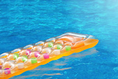 Summer pool dream. Multicolored inflatable matress floating in a blue swimming summer pool, dream, dreaming on summer days Stock Image