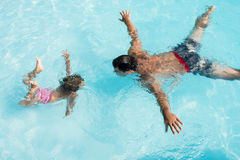 Summer in the pool. Father and daughter dive into the pool. Synchronous underwater acrobatics Stock Images