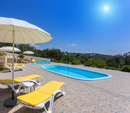 Summer pool with garden and sun loungers. Stock Photos