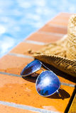 Summer Pool Party. A pair of sunglasses and summer straw hat resting on bricks alongside a sparkling pool Royalty Free Stock Images
