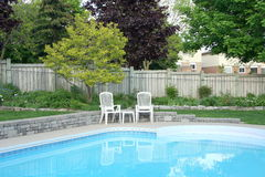 Summer Poolside. Two empty chairs on a pool patio Royalty Free Stock Images