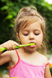 Summer portrait of adorable little girl brushing t. Summer portrait of cute little girl brushing teeth Stock Photography