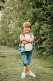 Summer portrait of adorable kid boy. Wearing colorful shirt and denim shorts, playing in the park on a nice sunny day Stock Photos