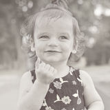 Summer portrait of beautiful baby girl. Black and white image. Kid smiling and looking at camera. Stock Photo