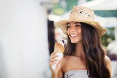 Summer portrait of beautiful woman with ice cream outdoors. Summer portrait of beautiful woman with hat eating ice cream outdoors stock photography