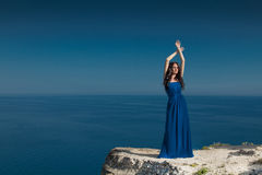Summer portrait. Beautiful woman standing on a cliff over blue s Stock Photography