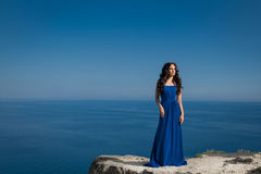 Summer portrait. Beautiful woman standing on a cliff over blue s Royalty Free Stock Photography