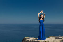 Summer portrait. Beautiful woman standing on a cliff over blue s Royalty Free Stock Photos