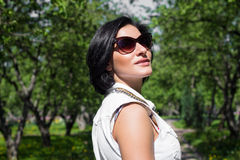 Summer portrait of a beautiful woman in sunglasses at the park Royalty Free Stock Photos