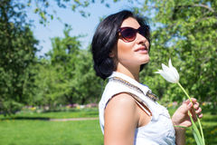 Summer portrait of a beautiful woman in sunglasses at the park with white tulips Stock Photography