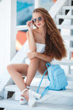 Summer portrait of a beautiful woman on the white steps Stock Image