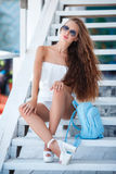 Summer portrait of a beautiful woman on the white steps Stock Photos