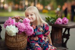 Portrait of a beautiful young blonde girl sitting next to a basket of flowers royalty free stock photos