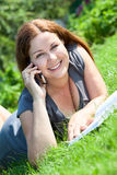 Summer portrait of beautiful young woman with cellphone on grass Stock Photo