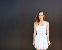 Summer portrait of a beautiful young woman in a short white dress. The wind blows her hair. Dark background. Warm colors. Royalty Free Stock Photography