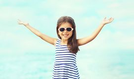 Summer portrait close-up happy smiling child raising hands up having fun. On sea royalty free stock photo