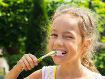 Summer portrait of cute girl brushing teeth Stock Photography