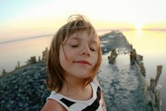Summer portrait of a girl close-up, on a salt lake in the sunset, girl with contented and playful faces. Posing for a photo royalty free stock photography