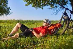 Summer portrait of handsome young man lying on green meadow near bike and backpack. Royalty Free Stock Photography