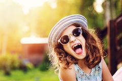 Summer portrait of happy kid girl on vacation in sunglasses and hat. Laugh and showing tongue royalty free stock photo