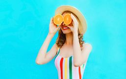 Summer portrait happy smiling woman holding in her hands two slices of orange fruit hiding her eyes in straw hat on colorful blue royalty free stock image