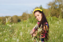 Summer portrait of happy young woman. Beautiful young woman with wreath of flowers on head in a field among the tall grass on a summer evening Stock Photo