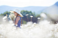 Summer portrait of a little girl in a field of white daisies. Girl,brunette with long hair braided in two braids,a large white straw hat,blue overalls,in the Stock Images