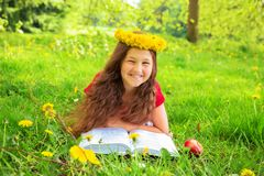 Merry child reads book among the dandelions. Summer portrait, merry child among the dandelions. Smiling girl with crown of dandelions flowers lies on the green royalty free stock photography