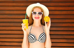 Summer portrait pretty smiling woman holds in hands juice fruit cup and orange Royalty Free Stock Photography