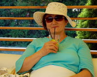 Summer portrait of senior lady. Senior lady with hat and sunglasses in summer holiday drinking a refreshing cocktail Stock Photo