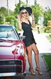 Summer portrait of stylish blonde vintage woman with long legs posing near red retro car. Fashionable attractive fair hair female Stock Photography