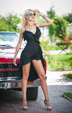 Summer portrait of stylish blonde vintage woman with long legs posing near red retro car. Fashionable attractive fair hair female Royalty Free Stock Photos