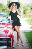 Summer portrait of stylish blonde vintage woman with long legs posing near red retro car. fashionable attractive fair hair female. With black hat near a red Royalty Free Stock Photography